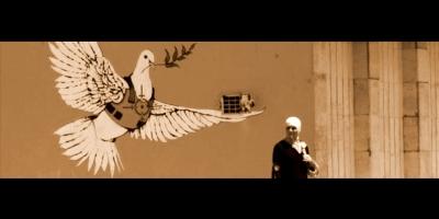 Grafiti tras mujer musulmana paseando: muestra una paloma de la paz con un chaleco antibalas