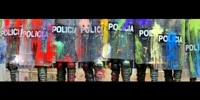 Policía manchada: policía con escudos y uniformes manchados de pintura de colores